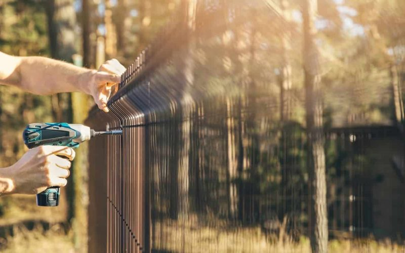 Fencing worker installing metal wire mesh fence panel